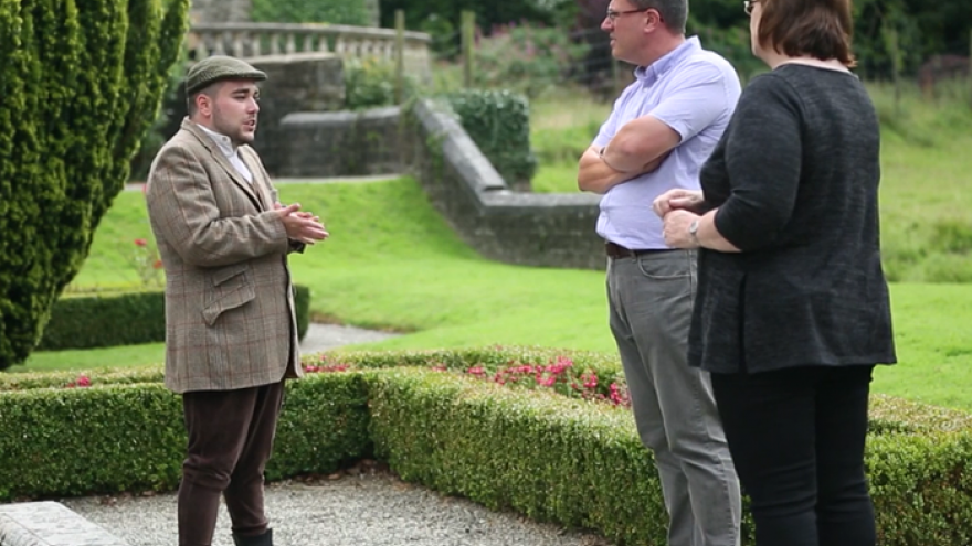 Man stood speaking with two other people in grounds of National Trust property.