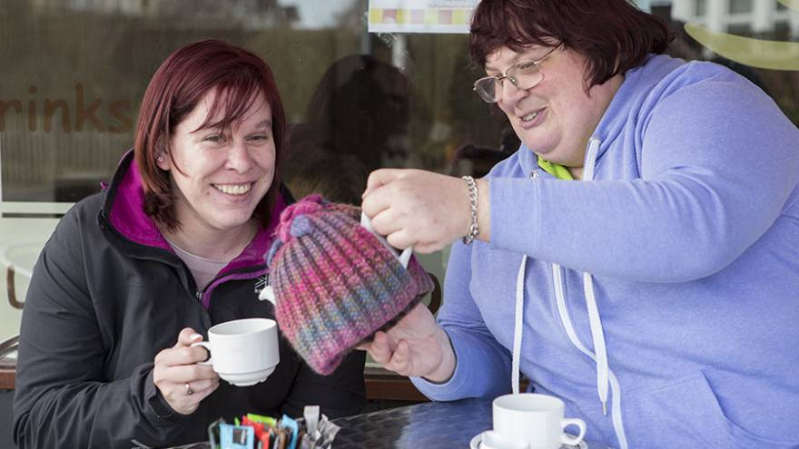 Two women sat at a table outside a cafe. One woman is pouring the other a cup of tea from a teapot.