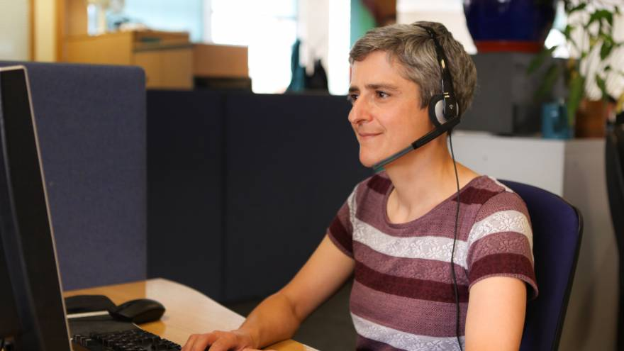 Woman with short grey and purple striped top. She is sat at a desk in an office with a computer on it. She is smiling whilst wearing a telephone headset.