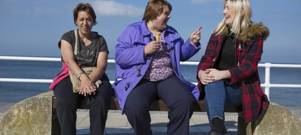 Three women sat on stone bench in front of seafront